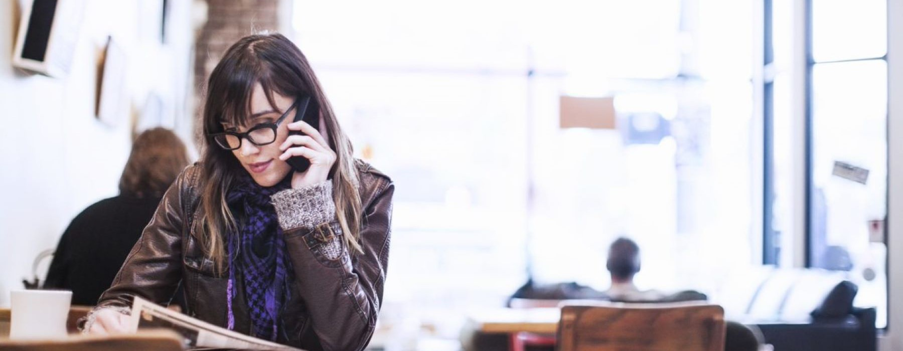 smartly dressed young woman on a phone, looking at a menu in neighborhood cafe